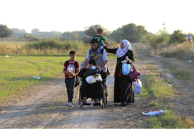 Syrian migrants travel along a road after crossing into Hungary from the border with Serbia near Roszke, Hungary