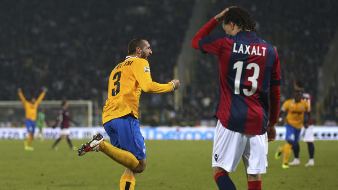 Juventus' Giorgio Chiellini celebrates past Bologna midfielder Diego Laxalt, of Uruguay, after scoring during the Serie A soccer match between Bologna and Juventus at the Dall' Ara stadium in Bologna, Italy, Friday, Dec. 6, 2013. Juventus won 2-0