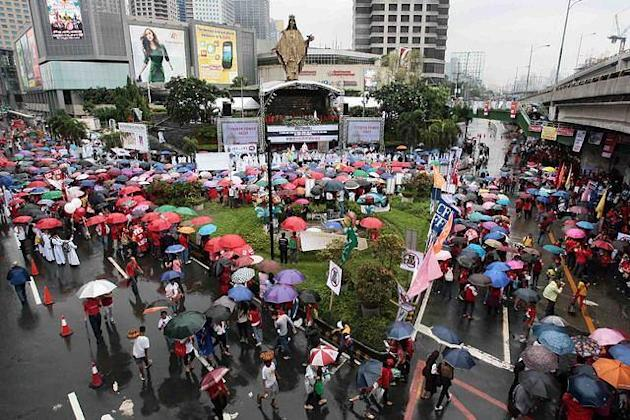 Catholic devotees use umbrellas against the rain as they join the Prayer Power against the Passage of the Reproductive Health (RH) Bill held at the Edsa Shrine along Epifanio Delos Santos Avenue (EDSA) in Quezon City, east of Manila. The Philippine Catholic church led by the Catholic Bishops Conference of the Philippines (CBCP) urged the faithful to show force on August 4, three days before the House of Representatives votes on the RH Bill on August 7. (Mike Alquinto/NPPA Images)