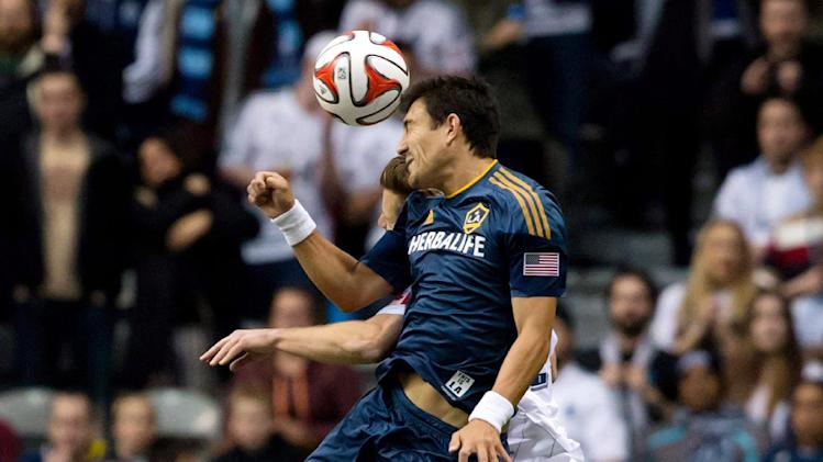 Los Angeles Galaxy's Stefan Ishizaki, left, of Sweden, and Vancouver Whitecaps' Jordan Harvey vie for the ball during the first half of an MLS soccer game Saturday, April 19, 2014, in Vancouver, British Columbia