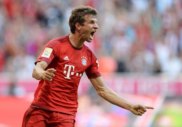Bayern Munich's striker Thomas Mueller celebrates after scoring the first goal for Munich during the German first division Bundesliga match against Bayer 04 Leverkusen in Munich on August 29, 2015