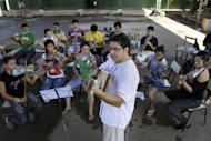 "In this Dec. 11, 2012 photo, Music Director Fabio Chavez leads his students from ""The Orchestra of Instruments Recycled From Cateura"" in a practice session in Cateura, a vast landfill outside Paraguay's capital of Asuncion, Paraguay. Chavez had learned clarinet and guitar as a child, and had started a small music school in another town in Paraguay before he got a job with an environmental organization teaching trash-pickers in Cateura how to protect themselves. Chavez opened a tiny music school at the landfill hoping to keep youngsters out of trouble. But he had just five instruments to share. (AP Photo/Jorge Saenz)"