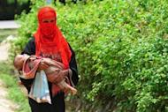 A Rohingya Muslim woman walks with her child at an unregistered refugee camp in Bangladesh after fleeing the violence in Myanmar. Jailed Islamist cleric Abu Bakar Bashir has threatened to wage war if Myanmar continues to harm Muslim Rohingyas, in a letter to the country's president Thein Sein seen on a website