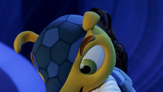 Fuleco dances on stage during the draw for the 2014 World Cup in Sao Joao da Mata