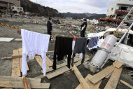 Naoe Mitsumata, 61, left, and his friend Ikuya Akazaki, 69, wait their laundries to dry near their houses damaged in the March 11 earthquake and tsunami in Otsuchi, Iwate Prefecture, Japan, Sunday, April 3, 2011.