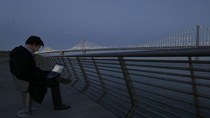 In this Wednesday, Feb. 20, 2013,  photo, Artist Leo Villareal poses for photographs as he operates lights on the San Francisco-Oakland Bay Bridge on Pier 14 in San Francisco. The San Francisco-Oakland Bay Bridge has been turned into the latest, and by far the biggest, backdrop for New York artist Leo Villareal, who has individually programmed 25,000 white lights spaced a foot apart on 300 of the span's vertical cables to create what is being billed as the world's largest illuminated sculpture. (AP Photo/Jeff Chiu)