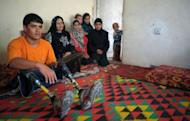 Afghan amputee Malek Mohammad (L) poses with his family at their home in Kabul. Malek appeared on television and newspaper articles were written about him after he won a local swimming competition in San Diego, California, and posed for a calendar of handicapped athletes