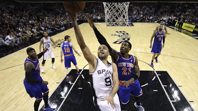 San Antonio Spurs' Tony Parker (9), of France, goes to the basket against New York Knicks' Iman Shumpert (21) during the second half on an NBA basketball game, Thursday, Jan. 2, 2014, in San Antonio. New York won 105-101