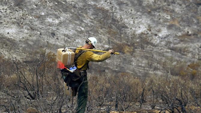 A firefighter carries tools down a burned hill after a wildfire in Point Mugu on Friday, May 3, 2013. A huge wildfire carved a path to the sea and burned on the beach Friday, but firefighters got a break as gusty winds turned into breezes. Temperatures remained high, but humidity levels were expected to soar as cool air moved in from the ocean and the Santa Ana winds retreated. (AP Photo/Nick Ut)