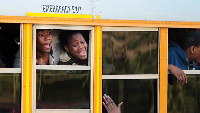 A student and parent react to seeing each other when buses arrive to unite parents and children at Emmanuel Baptist Church following a shooting at Price Middle school in Atlanta on Thursday, Jan. 31, 2013. A 14-year-old boy was wounded outside the school Thursday afternoon and a fellow student was in custody as a suspect, authorities said. No other students were hurt. (AP Photo/Atlanta Journal-Constitution, Curtis Compton)  MARIETTA DAILY OUT; GWINNETT DAILY POST OUT; LOCAL TV OUT; WXIA-TV OUT; WGCL-TV OUT