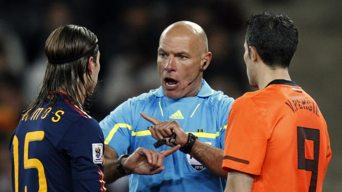 In this Sunday, July 11, 2010 file photo, referee Howard Webb of England, center, speaks with Spain's Sergio Ramos, left, and Netherlands' Robin van Persie during the World Cup final soccer match between the Netherlands and Spain at Soccer City in Johannesburg, South Africa. FIFA selected World Cup final referee Howard Webb on Wedensday Jan. 15, 2014, as one of the 25 who will officiate at the 2014 tournament in Brazil