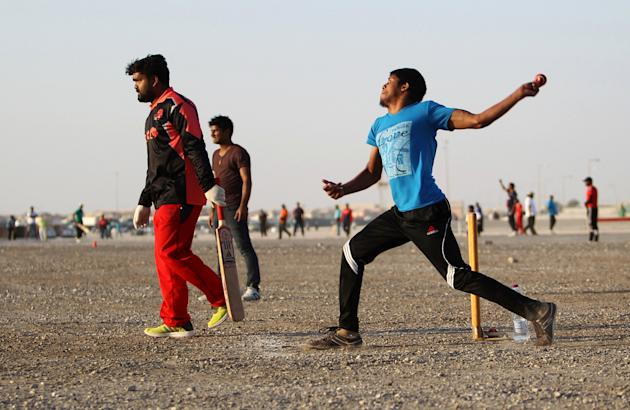 InMen play cricket during an excursion in Doha