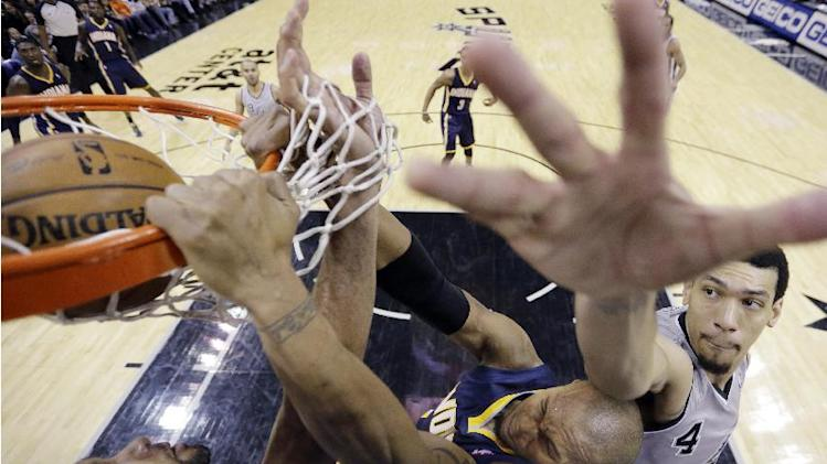 Indiana Pacers' David West, center, scores with a dunk over San Antonio Spurs' Tim Duncan, left, and Danny Green, right, during the second half of an NBA basketball game, Saturday, Dec. 7, 2013, in San Antonio