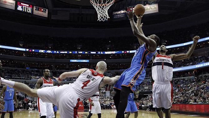 Oklahoma City Thunder forward Kevin Durant, front right, shoots as he is defended by Washington Wizards center Marcin Gortat (4), from Poland, and forward Trevor Ariza (1) in the first half of an NBA basketball game on Saturday, Feb. 1, 2014, in Washington. The Wizards won 96-81