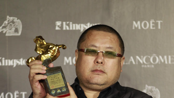 "Chinese director Gao QunShu holds his award for the Best Feature Film for the film ""Beijing Blues"" at the 49th Golden Horse Awards at the Luodong Cultural Working House in Yilan County, Taiwan, Saturday, Nov. 24, 2012. The Golden Horse awards are one of  the Chinese-language film industry's biggest annual events. (AP Photo/Chiang Ying-ying)"