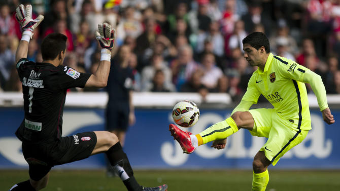 Barcelona's Luis Suarez, right, in action with Granada's goalkeeper Oier Olazabal, left, during a Spanish La Liga soccer match between Granada and FC Barcelona at Los Carmenes stadium in Granada, Spain, Saturday Feb. 28, 2015. (AP Photo/Daniel Tejedor)