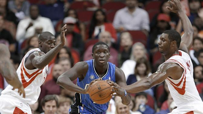Orlando Magic's Victor Oladipo, center, looks to pass the ball between Houston Rockets' Ronnie Brewer, left, and Terrence Jones in the second half of a preseason NBA  basketball game Wednesday, Oct. 16, 2013, in Houston