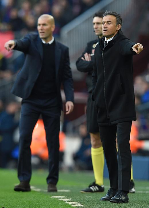 Barcelona's coach Luis Enrique (R) and Real Madrid's coach Zinedine Zidane (L) gesture from the sideline during the Spanish league football match FC Barcelona vs Real Madrid CF at the Camp Nou