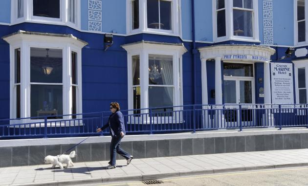 A woman walks her dog past the Marine Hotel on the repaired promenade in Aberystwyth