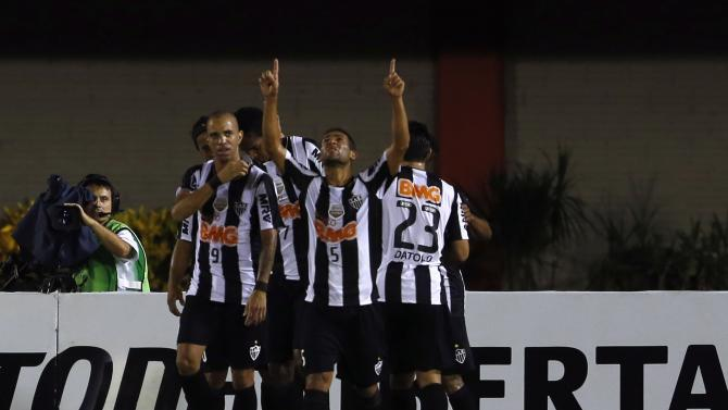 Jo of Brazil's Atletico Mineiro walks as teammates celebrate his goal against Paraguay's Nacional during their Copa Libertadores soccer match in Ciudad del Este