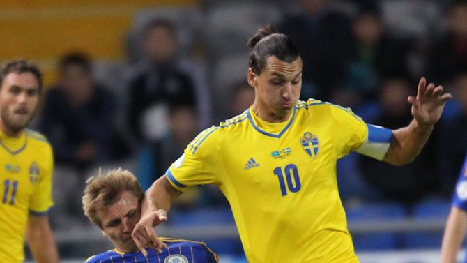 Kazakhstan's Valerij Korobkin, left, and Sweden's Zlatan Ibrahimovic fight for the ball during their World Cup group C qualifying soccer match in Astana, Kazakhstan, Tuesday, Sept. 10, 2013. (AP Photo)