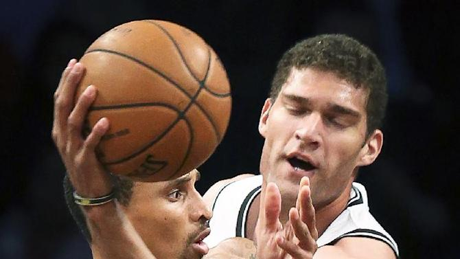 Indiana Pacers point guard George Hill (3) passes the ball past Brooklyn Nets center Brook Lopez (11) during the third quarter of a NBA basketball game, Saturday, Nov. 9, 2013, at the Barclays Center in New York. The Indiana Pacers defeated the Brooklyn Nets, 96-91
