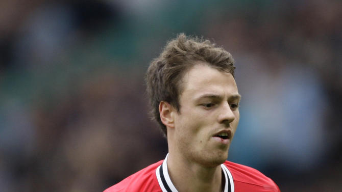 Manchester United's Jonny Evans leaves the pitch after being sent off during his team's 6-1 defeat by Manchester City in their English Premier League soccer match at Old Trafford Stadium, Manchester, England, Sunday Oct. 23, 2011. (AP Photo/Jon Super)