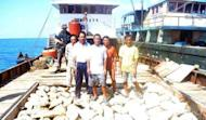 Philippine navy officers are pictured guarding Chinese fishermen aboard their fishing vessel loaded with giant shell clams which was intercepted off Scarborough Shoal, on April 11