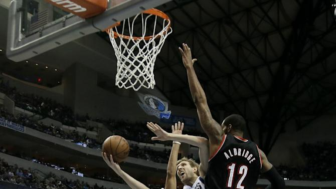 Dallas Mavericks forward Dirk Nowitzki (41) fights for a shot attempt against Portland Trail Blazers' LaMarcus Aldridge (12) and Nicolas Batum, rear, during the first half of an NBA basketball game, Saturday, Jan. 18, 2014, in Dallas. The Trail Blazers won 127-111