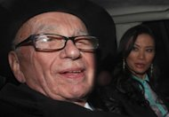 "News Corp Chief Rupert Murdoch and his wife Wendi Deng drive away from the High Court in central London on April 25. Murdoch has admitted there was a ""cover-up"" over phone hacking at Britain's News of the World tabloid but tried to shift the blame away from himself and senior executives at his media empire"