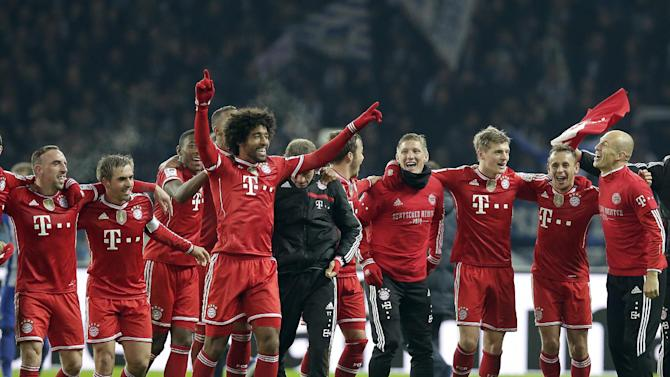 Bayern's Arjen Robben of the Netherlands, right, Bayern's Franck Ribery of France, left, and their teammates celebrate winning the German soccer championship after the German Bundesliga soccer match between Hertha BSC Berlin and Bayern Munich in Berlin, Germany, Tuesday, March 25, 2014
