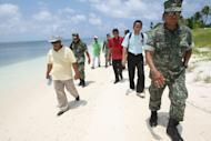 Armed Forces of the Philippines Western Command commander Lt. Gen. Juancho Sabban, right, Kalayaan municipality Mayor Eugenio Bito-onon, 2nd right, and Philippine Congressman Walden Bello, 3rd right, walk along the shores of Pagasa Island, part of the disputed Spratly group of islands, in the South China Sea located off the coast of western Philippines Wednesday, July 20, 2011. China protested a trip made by Filipino lawmakers to disputed areas in the South China Sea to assert the claim of the Philippines. Ethan Sun, spokesman for the Chinese embassy in Manila, said the trip scheduled was 'against the spirit' of a code of conduct signed by claimants to the areas in 2002. The Spratlys, believed to be rich in oil, mineral and marine resources, are also claimed in whole or partly by Brunei, Malaysia, Vietnam and Taiwan. (AP Photo/Rolex Dela Pena, Pool)