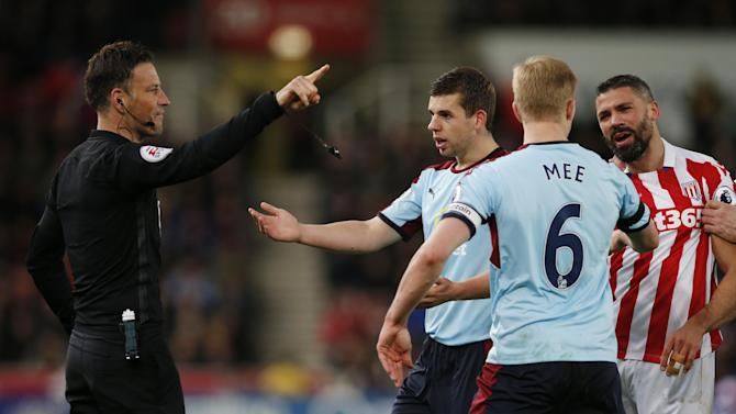 Referee Mark Clattenburg speaks with Burnley's Jon Flanagan, Ben Mee and Stoke City's Jonathan Walters