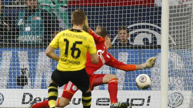 Borussia Dortmund's Blaszcykowski scores a goal past Schalke 04 goalkeeper Hildebrand during their German first division Bundesliga soccer match at the Schalke Arena in Gelsenkirchen