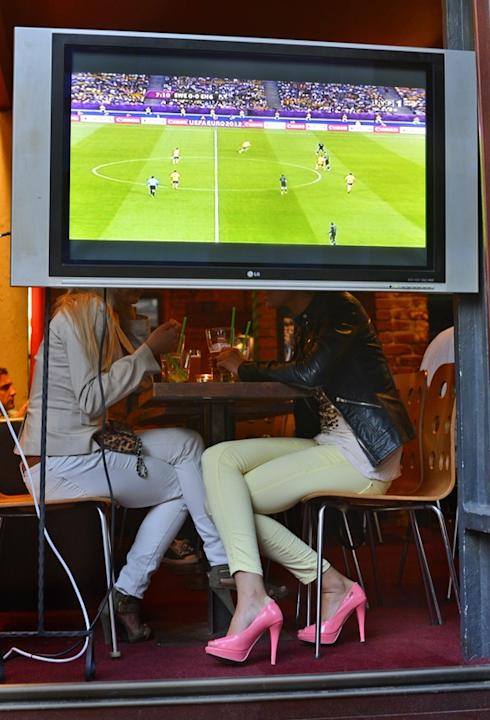 Two Woman Have A Drink Behind A TV Showing The Match Sweden Vs. England AFP/Getty Images