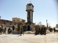 Syrian soldiers gather in front of a badly damaged clock tower on top of which flies a Syrian flag in the main square of the city of Qusayr on June 5, 2013. The United States condemned an assault by Syrian troops on Qusayr, claiming the regime had relied on Hezbollah to win the battle and caused tremendous suffering
