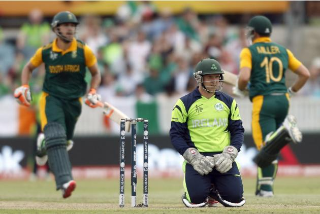 Ireland's wicketkeeper Gary Wilson rests on his knees as South Africa's David Miller and Rilee Rossouw run between wickets during their Cricket World Cup match at Manuka Oval in Canberra