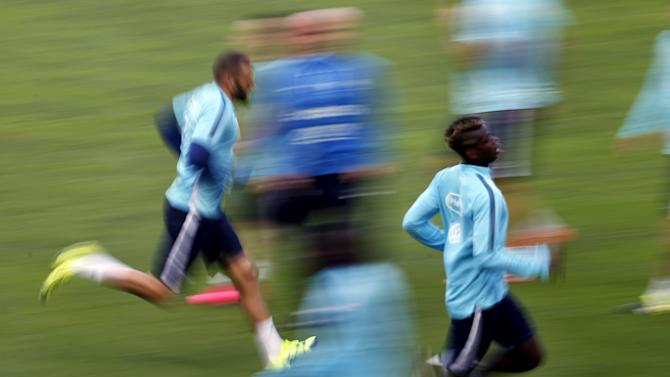 France's national soccer team players Karim Benzema and Paul Pogba run during a training session at Alvalade stadium in Lisbon