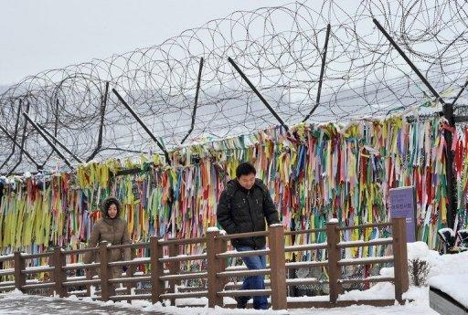 "Visitors walk past barbed wire covered with ""reunification ribbons"" near the Demilitarized Zone (DMZ) dividing the two Koreas on January 1, 2013. The number of North Korean refugees fleeing to the South fell sharply last year, officials in Seoul said, with activists citing crackdowns and tighter border controls."
