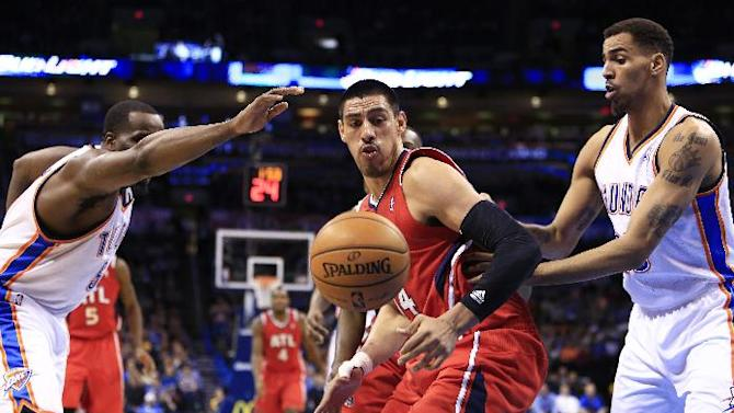 Atlanta Hawks forward Gustavo Ayon, center, and Oklahoma City Thunder center Kendrick Perkins (5) and guard Thabo Sefolosha (25)  go after a loose ball during the second quarter of an NBA basketball game, Monday, Jan. 27, 2014, in Oklahoma City