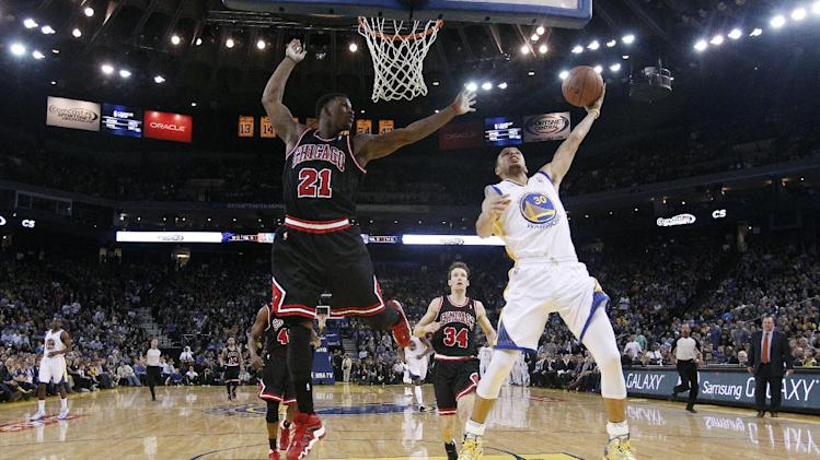 Golden State Warriors' Stephen Curry (30) scores past Chicago Bulls' Jimmy Butler (21) during the second half of an NBA basketball game on Thursday, Feb. 6, 2014, in Oakland, Calif. Golden State won 102-87