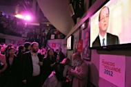 Socialist party loyalists gather to watch on TV the televised national debate between Francois Hollande and Nicolas Sarkozy at the Players bar in Paris. Sarkozy launched fierce assaults on his rival Hollande in their pre-poll debate but failed to land a decisive blow