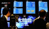 A TV cameraman films a share price index at the Tokyo Stock Exchange, 2011. Asian markets were mixed as dealers cautiously await a crucial bond auction in Spain, while Wall Street provided a soft lead after falling on disappointing corporate earnings
