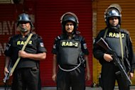Bangladeshi Rapid Action Battalion (RAB) personnel stand guard during a nationwide strike in Dhaka on March 4, 2013. Schools and businesses were shut Monday across Bangladesh on the second day of a general strike called by Islamist protesters, as three more demonstrators died in the deadliest violence since independence