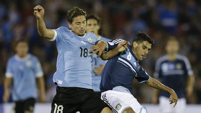 Uruguay's Gaston Ramirez, left, fight for the ball with  Argentina's Augusto Fernandez during a 2014 World Cup qualifying soccer match  in Montevideo, Uruguay, Tuesday, Oct. 15, 2013