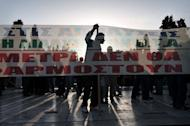 """A protester's silhouette is seen behind a banner reading: """"The measures won't apply"""", as demonstrators gather in front of the parliament in Athens on April 28, 2013"""