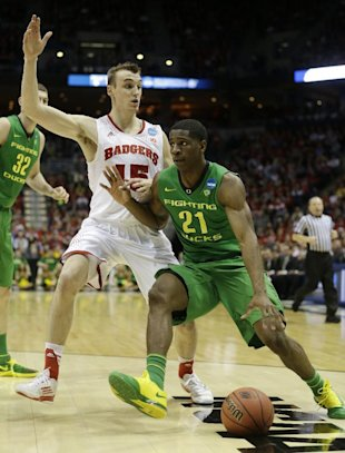 Oregon guard Damyean Dotson (21) drives the ball against Wisconsin forward Sam Dekker (15) during the first half of a third-round game of the NCAA college basketball tournament Saturday, March 22, 2014, in Milwaukee. (AP Photo/Morry Gash)
