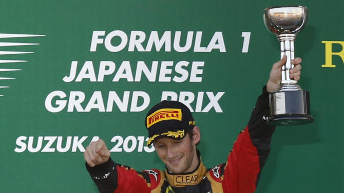 Third-placed Lotus Formula One driver Grosjean of France raises his trophy on the podium after the Japanese F1 Grand Prix at the Suzuka circuit