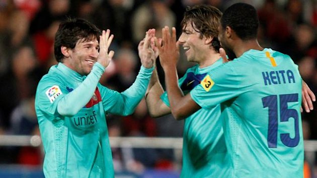 Barcelona's Lionel Messi (L) celebrates his goal against Mallorca with teammates Scherer Maxwell and Seydou Keita (R) during their Spanish First Division soccer match at Iberostar stadium in Palma de Mallorca February 26, 2011