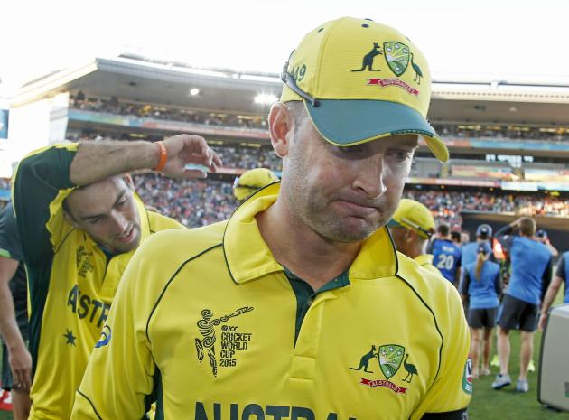 Australia's captain Clarke leads some teammates off the field after losing to New Zealand during their Cricket World Cup match in Auckland